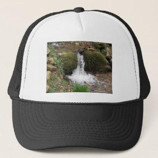 Little waterfall by mossy rocks in the forest trucker hat