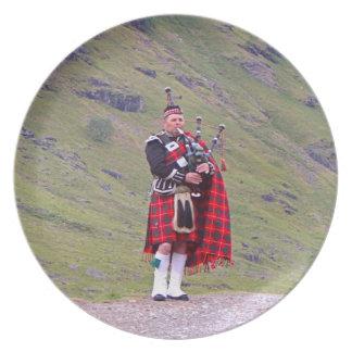 Lone Scottish bagpiper, Highlands, Scotland Plate