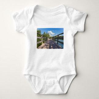 Long wooden bridge over water of pond baby bodysuit