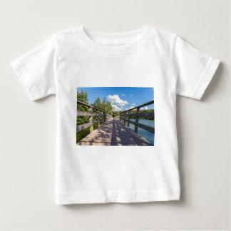Long wooden bridge over water of pond baby T-Shirt