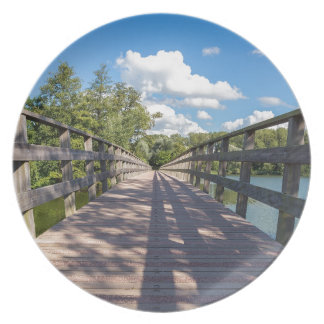 Long wooden bridge over water of pond plate