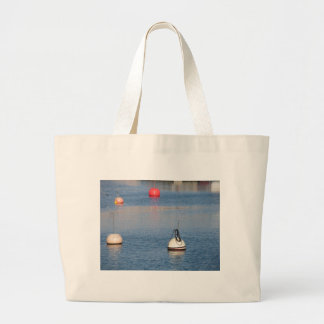 Lots of mooring buoys floating on calm sea water large tote bag