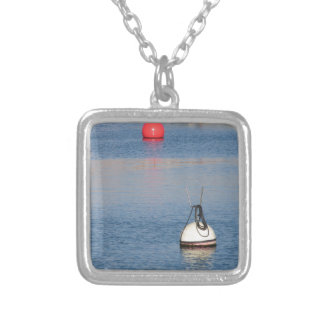 Lots of mooring buoys floating on calm sea water silver plated necklace