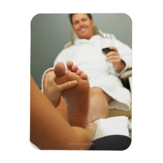 Low angle view of man receiving foot massage rectangular photo magnet