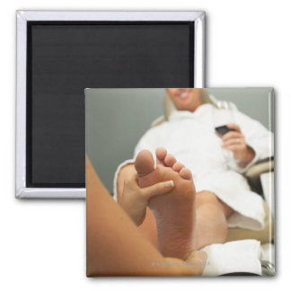 Low angle view of man receiving foot massage square magnet