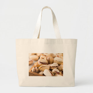 Macro close-up view of a group of salted pistachio large tote bag