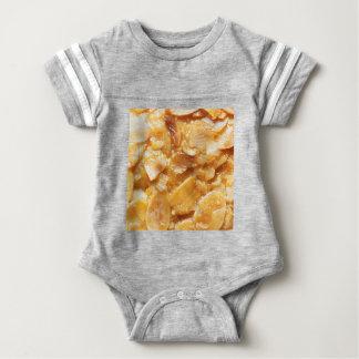 Macro of almond splitters on a cake baby bodysuit