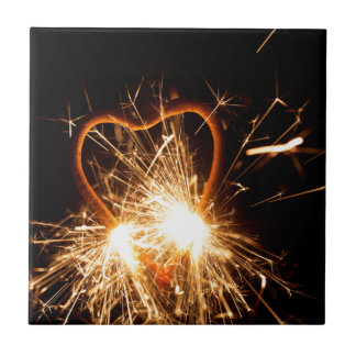 Macro photo of a burning sparkler in form of a hea ceramic tile