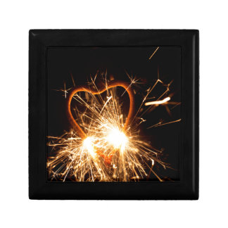 Macro photo of a burning sparkler in form of a hea gift box