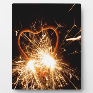 Macro photo of a burning sparkler in form of a hea plaque