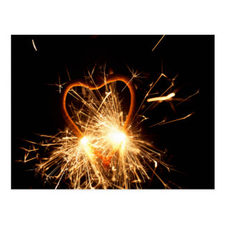 Macro photo of a burning sparkler in form of a hea postcard