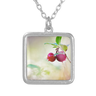 Macro shot of cowberry growing in forest. silver plated necklace
