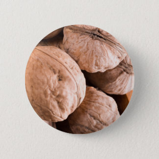 Macro view of a group of old walnuts 6 cm round badge