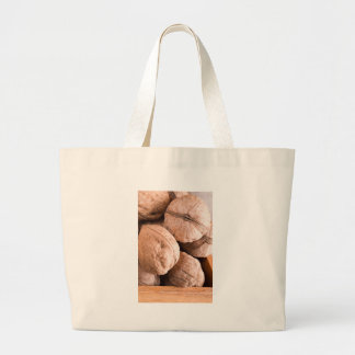 Macro view of a group of old walnuts large tote bag
