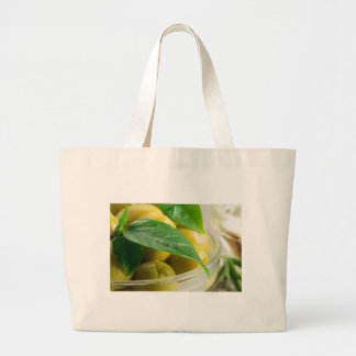 Macro view of the olives with green leaves large tote bag