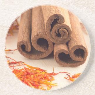 Macro view of the sticks of cinnamon and saffron coaster