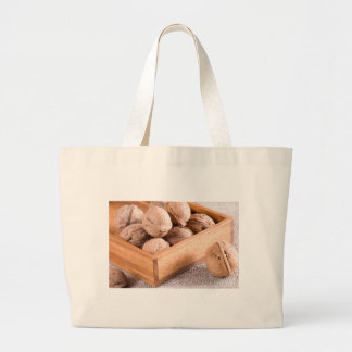 Macro view of walnuts close up in a wooden box large tote bag