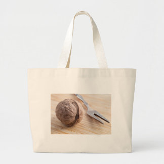 Macro view on walnuts and fork close-up large tote bag