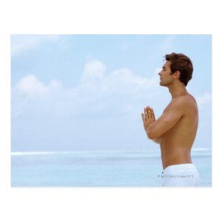 Maldives, Smart young guy practicing yoga at Postcard