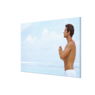 Maldives, Smart young guy practicing yoga at Stretched Canvas Print