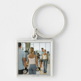 Man and woman lifting hand weights in front of a Silver-Colored square key ring