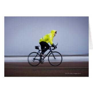 Man bicycles on a cold and foggy winter day. greeting cards