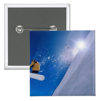 Man flying through the air on a snowboard with 15 cm square badge