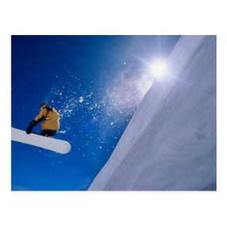 Man flying through the air on a snowboard with postcard