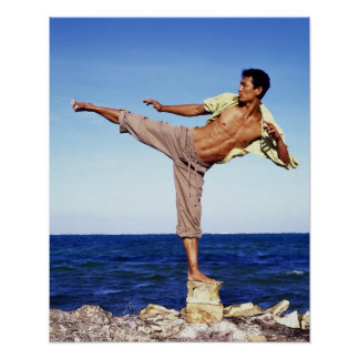 Man in martial arts kicking position, on beach, poster