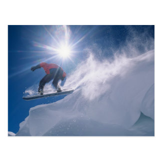 Man jumping off a large cornince on a snowboard postcard