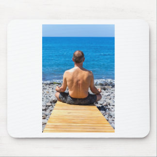Man meditating at beach and sea mouse pad