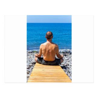 Man meditating at beach and sea postcard