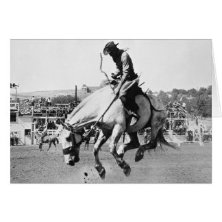 Man riding bucking horse in rodeo card