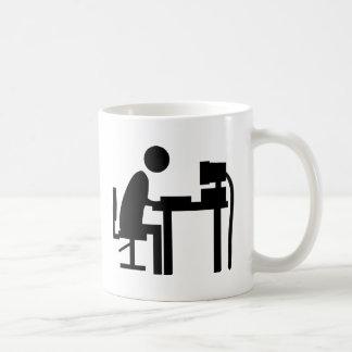 Man sat at a computer. coffee mug