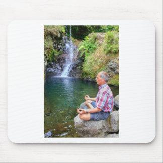 Man sitting on rock meditating near waterfall mouse pad