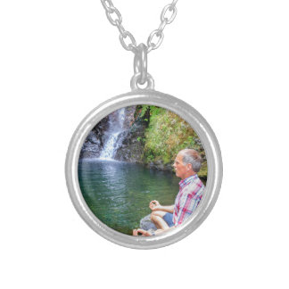 Man sitting on rock meditating near waterfall silver plated necklace