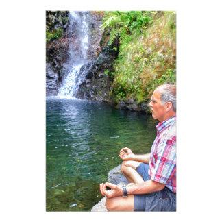 Man sitting on rock meditating near waterfall stationery