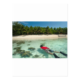 Man snorkeling off a tropical island postcard