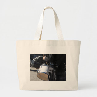 Man with kilt playing on drums large tote bag