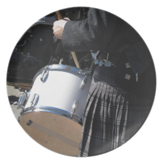 Man with kilt playing on drums plate