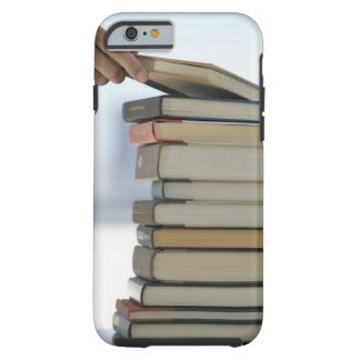 Man's hand taking a book from a stack of books tough iPhone 6 case