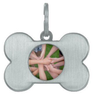Many arms of children holding hands together pet tag