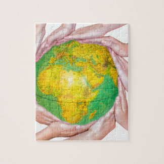 Many arms of children with hands holding globe jigsaw puzzle