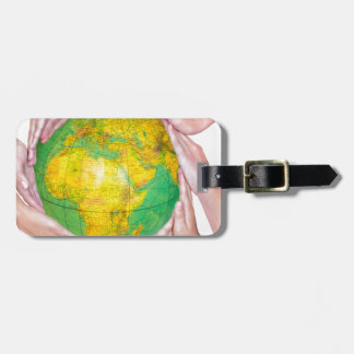 Many arms of children with hands holding globe luggage tag