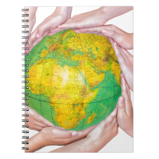 Many arms of children with hands holding globe notebooks