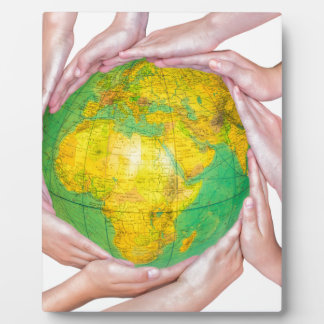 Many arms of children with hands holding globe plaque