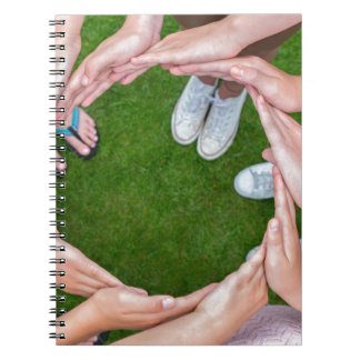 Many arms of children with hands making circle notebook