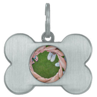 Many arms of children with hands making circle pet tag