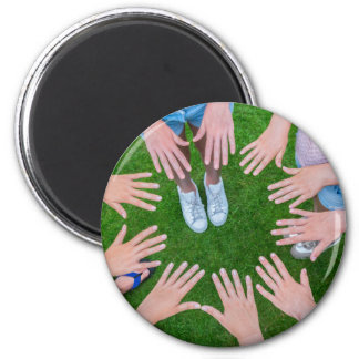 Many children hands joining in circle above grass magnet