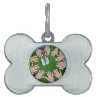 Many children hands joining in circle above grass pet name tag